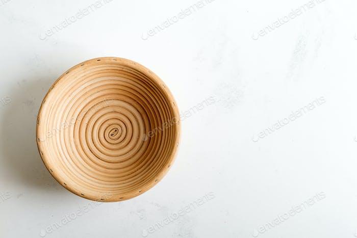 Handgefertigter Weidenkorb für hausgemachtes frisch gebackenes Gebäck auf einem hellgrauen Marmorhintergrund