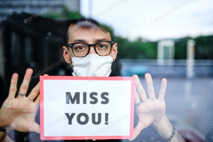 Portrait of sad man with face mask holding miss you sign, quarantine and lockdown concept