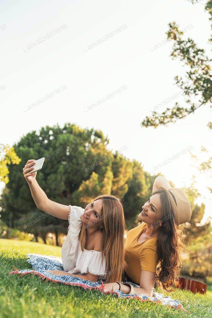 Schöne Frauen, die ein Selfie-Porträt im Park machen.