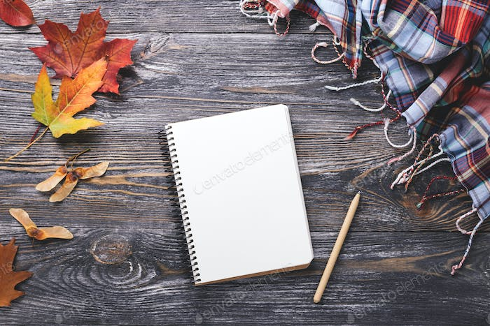 Autumn Leaves, Paper Notebook and Scarf on Wooden Background.