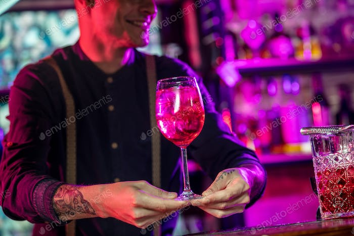 Barman proposing alcoholic cocktails, shots, beverages to guest in multicolored neon light