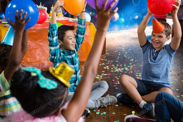 Cheerful children playing with balloon