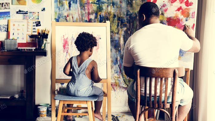 Black artist dad doing his art work with his child sitting nearby