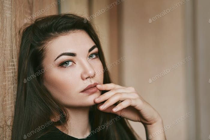 Woman with blue eyes poses in front of the camera. Beauty care