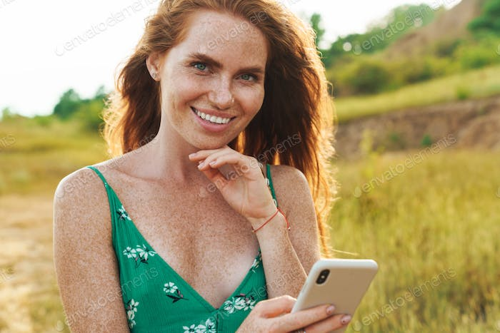 Happy woman in summer dress texting on a smart phone