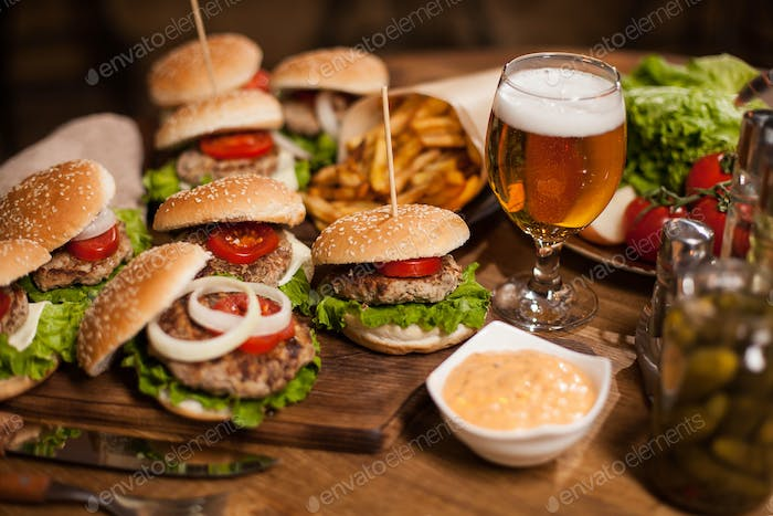Close up of fresh burgers with a glass of beer on vintage wooden table