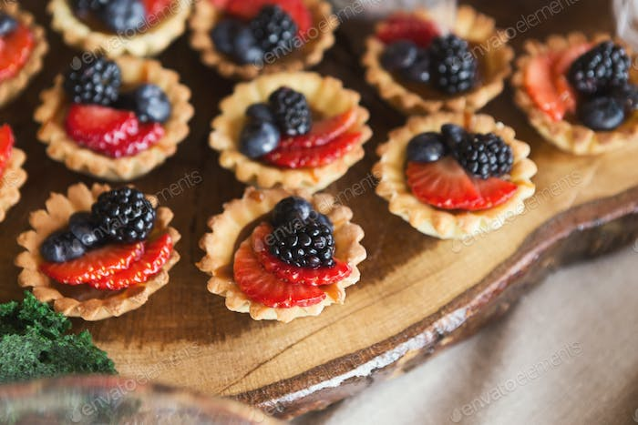 Small tartalettes with berries on wooden cutting board