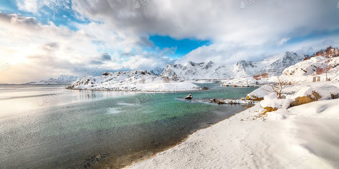 winter scenery with lots of snow  in small fishing village and snowy  mountain peaks