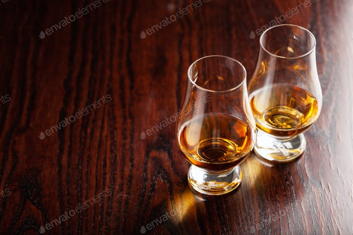 glass of whisky spirit brandy on dark brown background