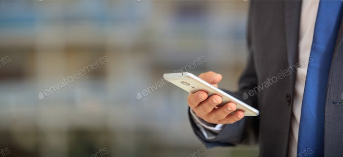 Man holding phone. Young businessman in business wear using a mobile, closeup view on smartphone