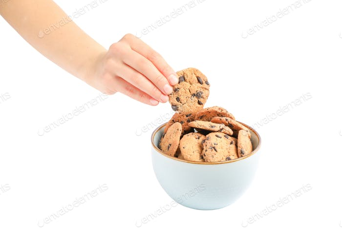 Young woman holding tasty chocolate chip cookie over bowl on white background, closeup