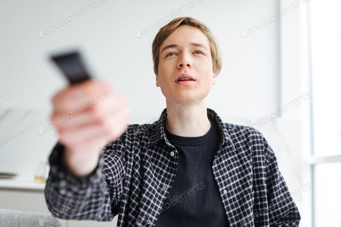 Young thoughtful man using a remote control while watching TV at home