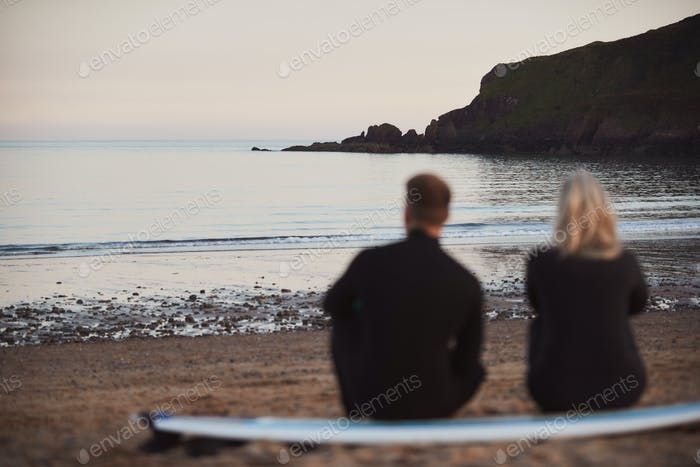 Defocused Shot Of Couple In Wetsuits On Surfing Staycation Sitting On Surfboard Looking Out To  Sea