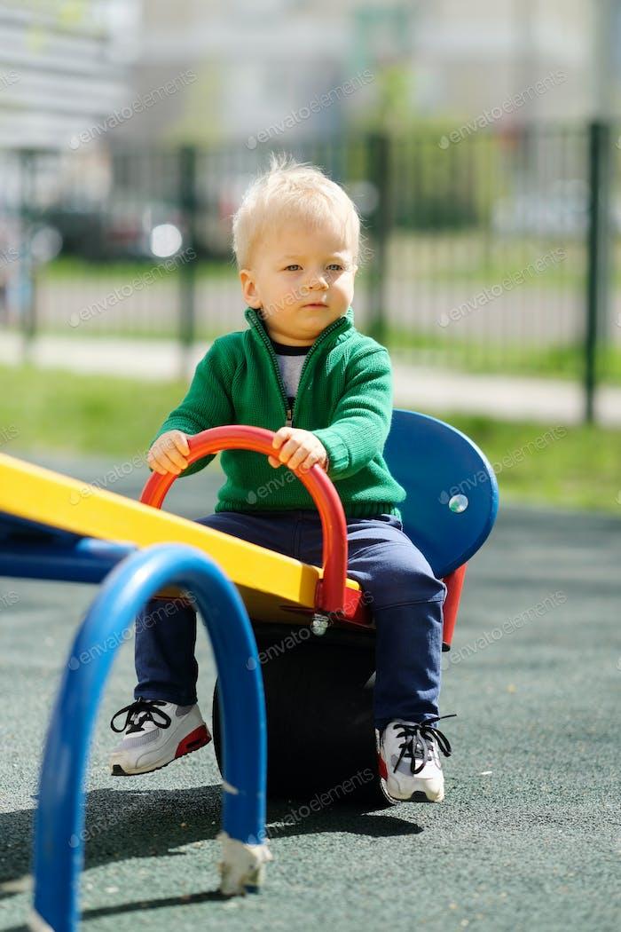 Uno Año de edad Bebé niño niño con suéter verde en el patio de recreo