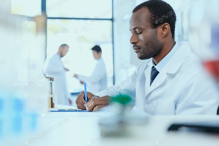 Afroamerikanischer Wissenschaftler im weißen Mantel Notizen während der Arbeit im Labor, Labor