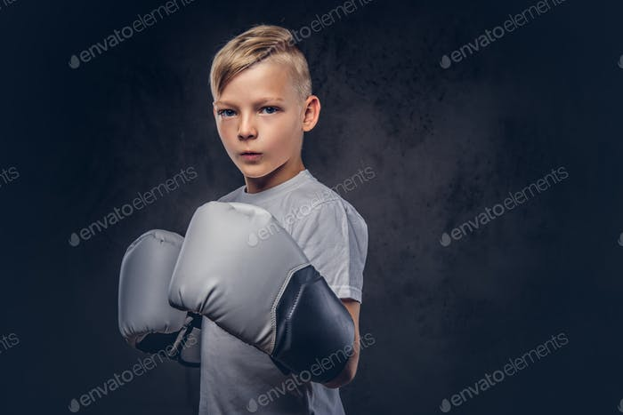 Handsome little boy boxer with blonde hair dressed in a white t-shirt in gloves ready to fight.