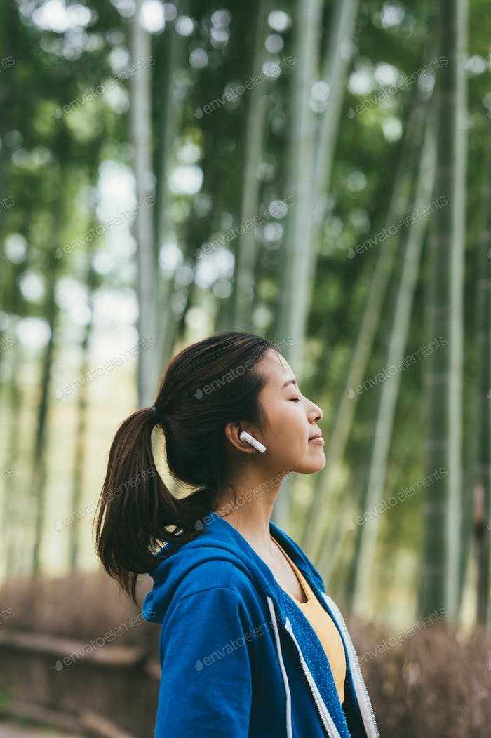 Young Asian woman using earphones outdoors
