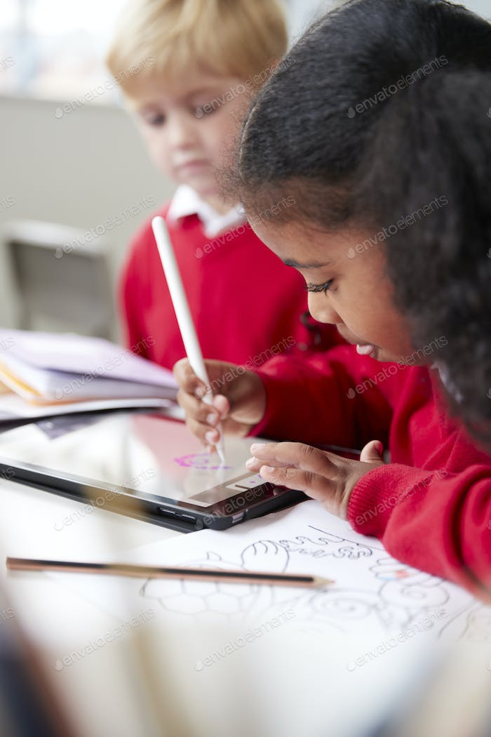 Schoolgirl sitting next to a boy in an infant school classroom, using a tablet computer and stylus