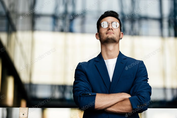 Architect in glasses dressed in stylish clothes stands on the background of a modern glass building