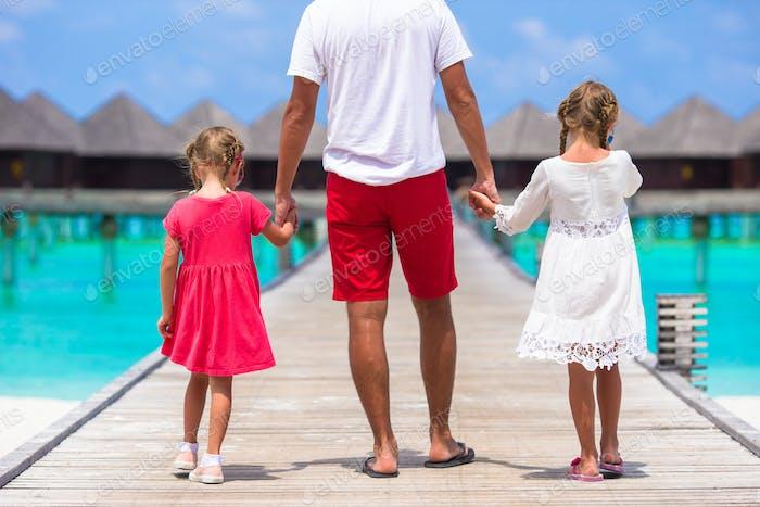 Kleine Mädchen mit Papa auf Holzsteg in der Nähe von Wasser Bungalow im exotischen Resort