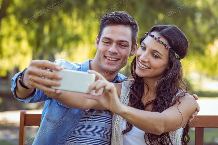 Cute couple taking a selfie in the park on a sunny day