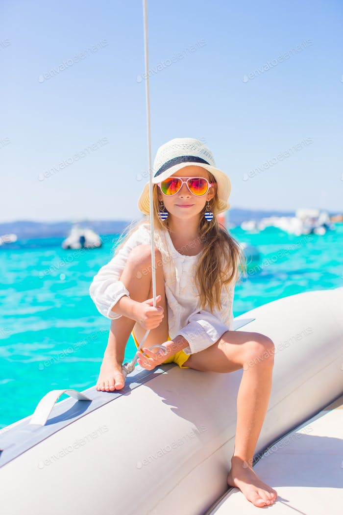 Little girl enjoying sailing on boat in the open sea