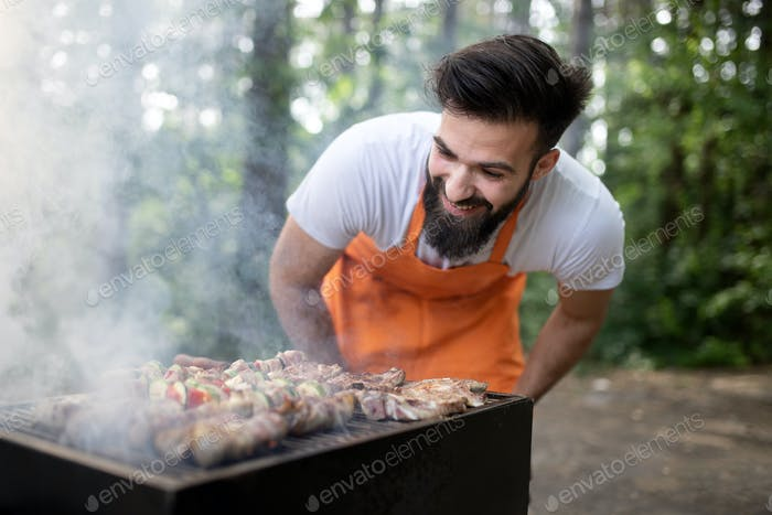 Handsome male preparing barbecue, grill outdoors for friends