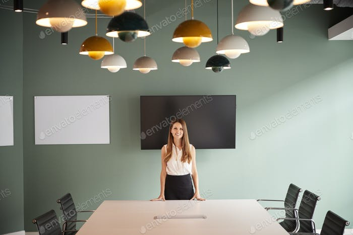 Portrait Of Young Businesswoman Standing By Boardroom Table