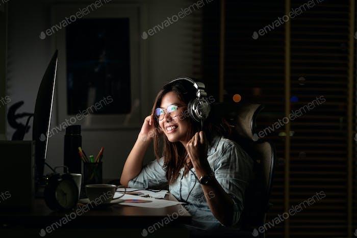 Porträt einer asiatischen Geschäftsfrau, die die Musik über Kopfhörer und Smartphone hört