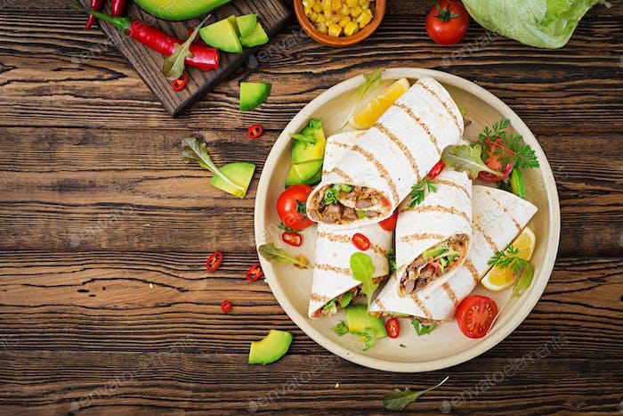 Burritos wickelt mit Rindfleisch und Gemüse auf einem hölzernen Hintergrund.