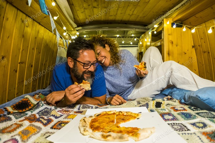 Couple have fun eating pizza inside vintage hand made wooden van vehicle in alternative lifestyle