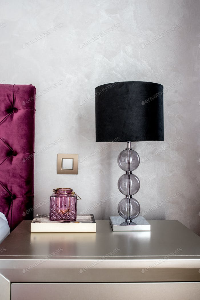 Close up details of lamp on nightstand in modern stylish bedroom