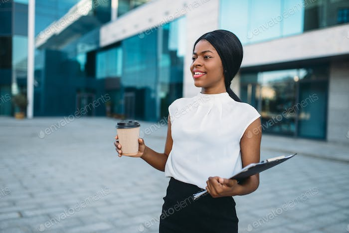 Female business person with coffee cup and notepad