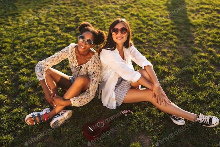 zwei ziemlich lächelnd Mädchen sitzen auf Gras glücklich suchen in cam