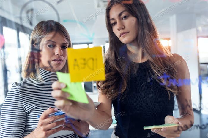 Two business young women working together on wall glass with post it stickers