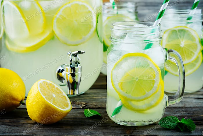 Homemade lemonade with mint, ice, and fresh lemon slices in mason jar