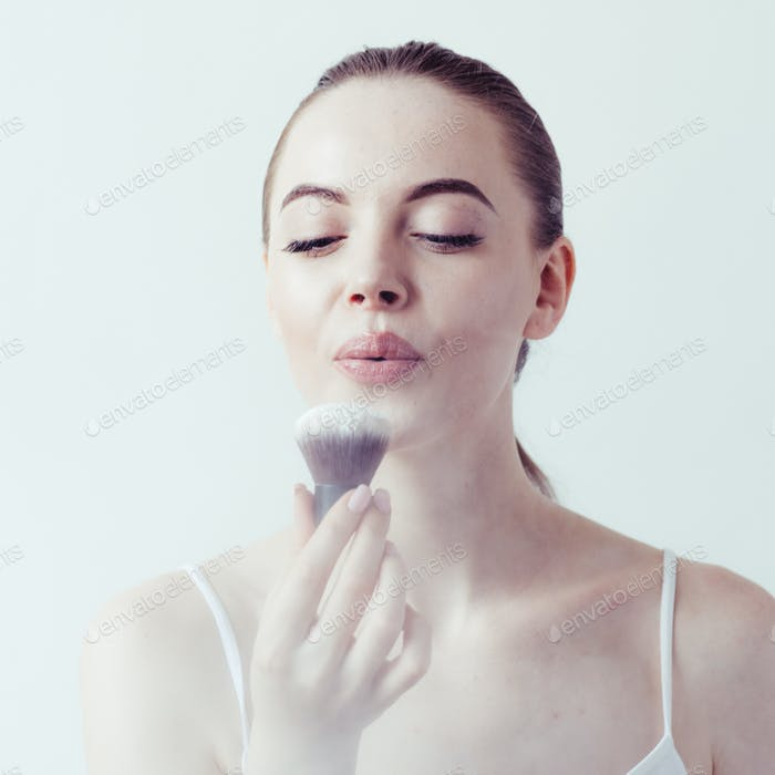 Woman makeup powder applying skin face  beautiful female natural portrait.
