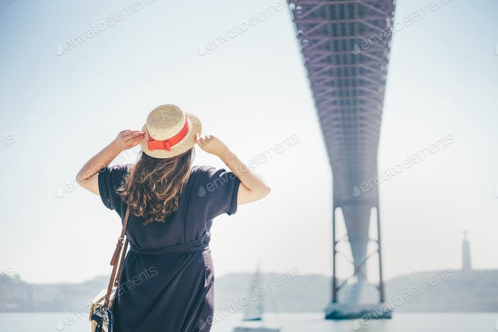 The girl looks at the bridge called April 25 in Lisbon in Portugal
