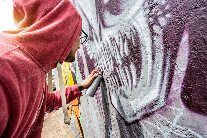 Street artist painting colorful graffiti on public wall