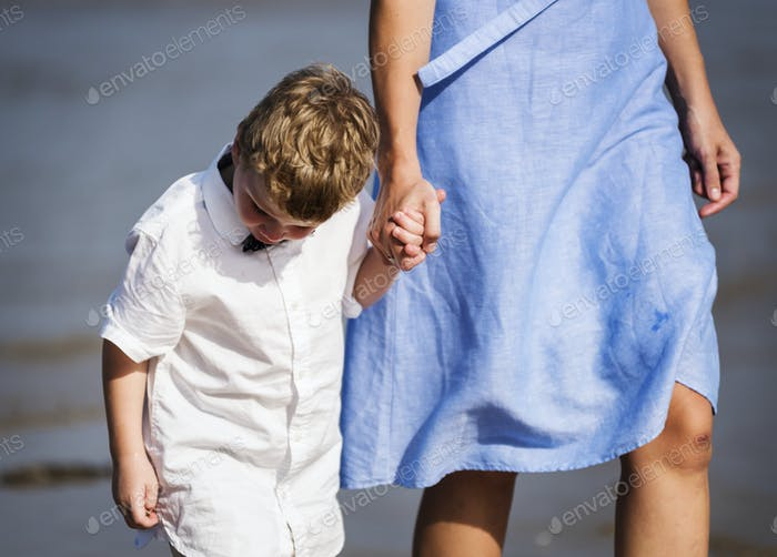 Mom and son walking on the beach