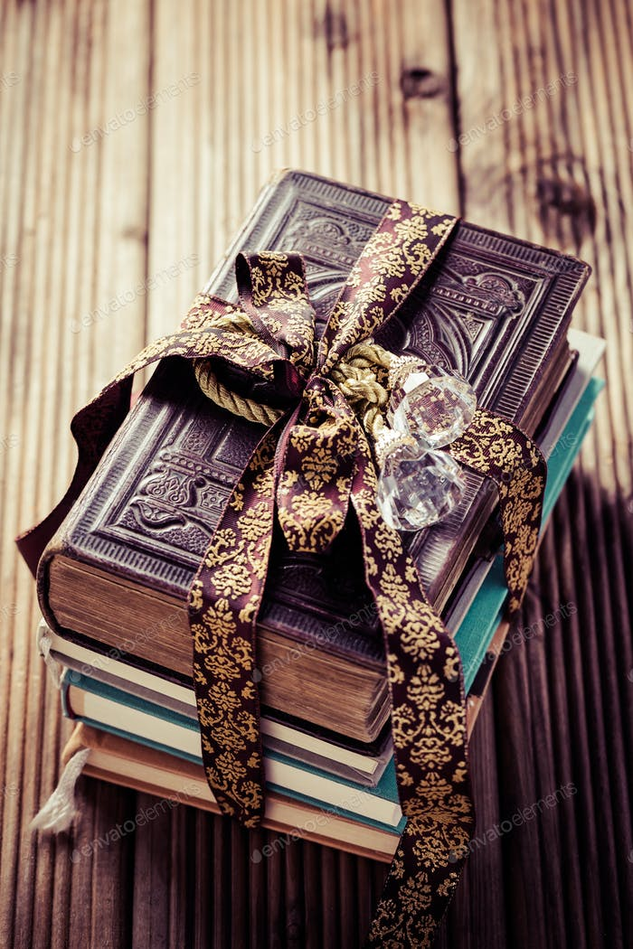 Stack of old books with vintage ribbon as present on wooden background