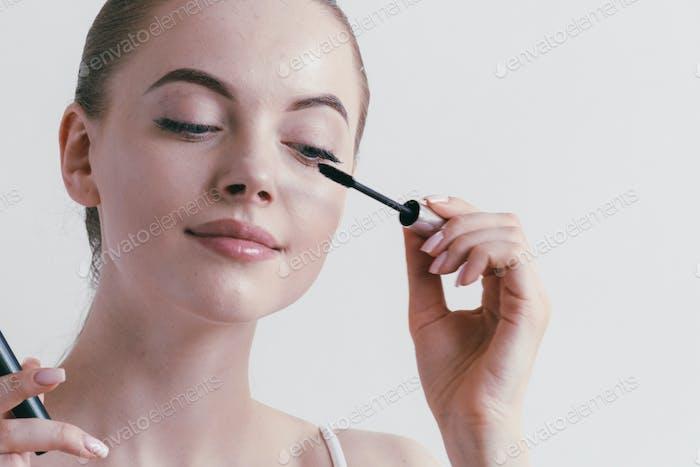Mascara woman portrait, beautiful brunette model applying brush mascars eyes lashes