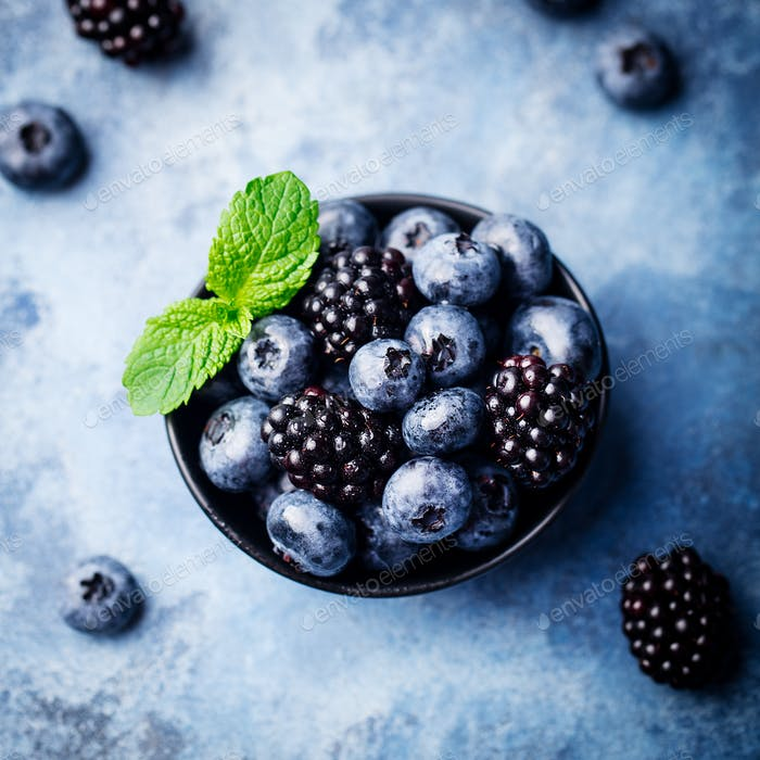 Blueberry and Blackberry Berries with Mint Leaves in Black Bowl on Blue Stone Background.