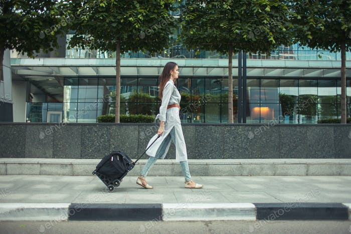 female walking on street with travel bag