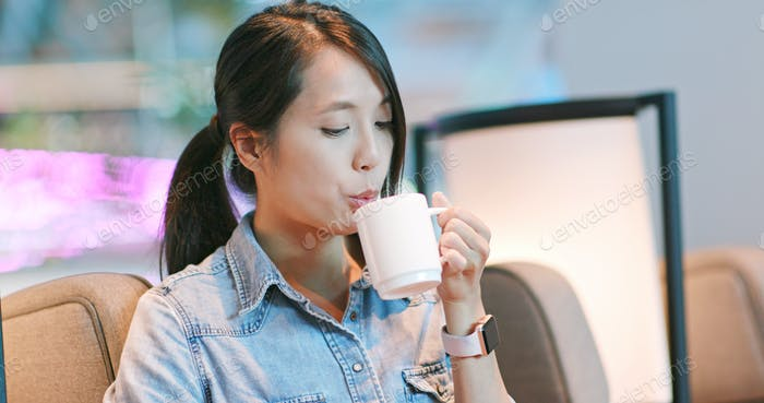 Woman enjoy drink of hot coffee in lounge