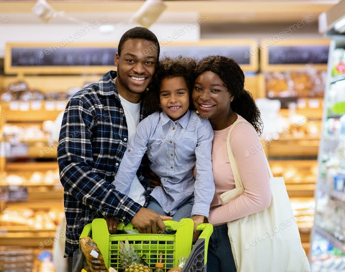 Happy black family with shopping cart purchasing food at supermarket