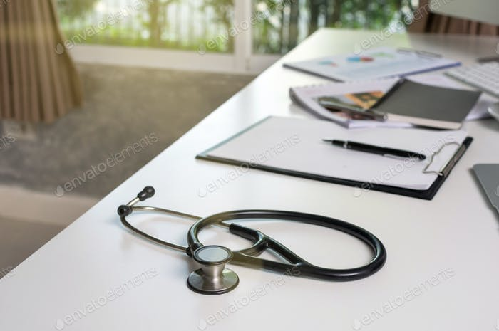 Stethoscope on the workplace table with some part of computer set and keyword