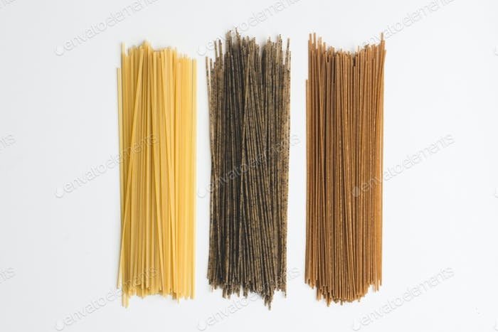 Whole-grain pasta spaghetti tricolora on a white background