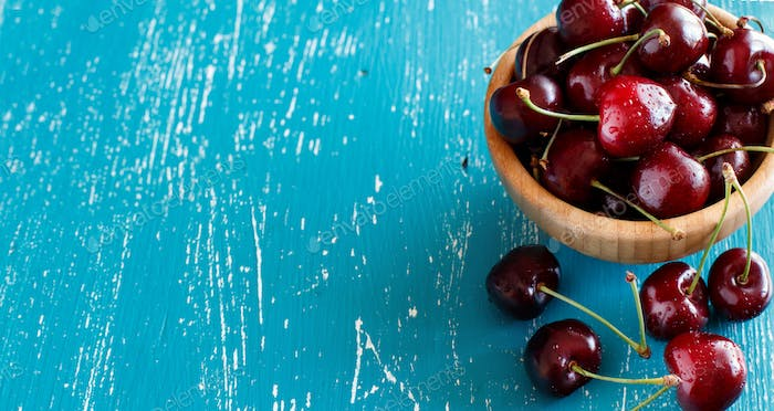Red cherries in a bowl on a blue wooden background