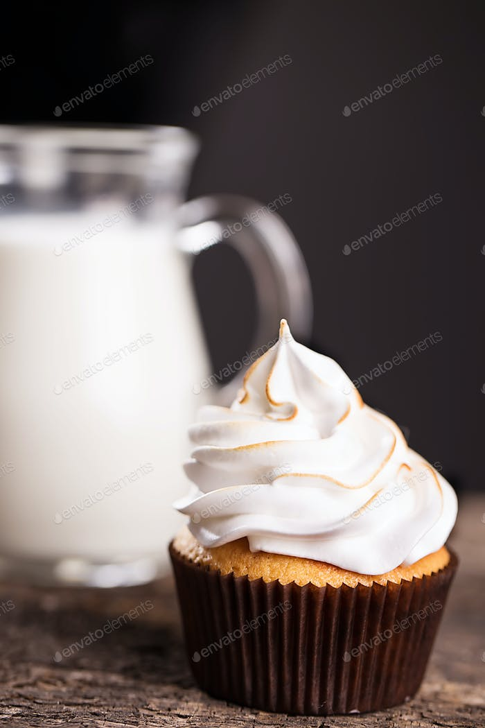 Delicious cupcakes with a carafe of milk